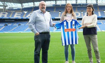 Mirari Uria posa con la camiseta de la Real Sociedad entre el consejero Alex Uranga y la directora deportiva Garbiñe Etxeberria